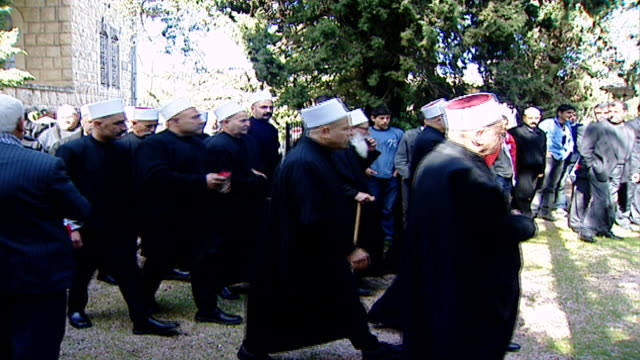 moukhtara palace. view of druze sheikhs, politicians and guests holding roses and walking towards the tomb of late druze leader kamal jumblatt to pay... - シャイフ点の映像素材/bロール