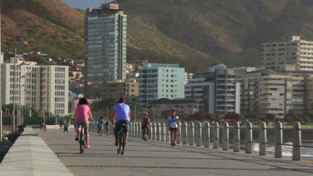 moulle point promenade with casual cyclists in front of lion's head and signal hill - cape town stock videos & royalty-free footage