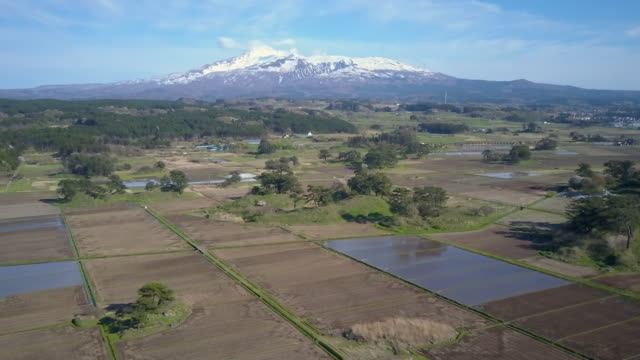 ws aerial mount chokai and rice paddies, yuza, yamagata prefecture, japan - 鳥海山点の映像素材/bロール