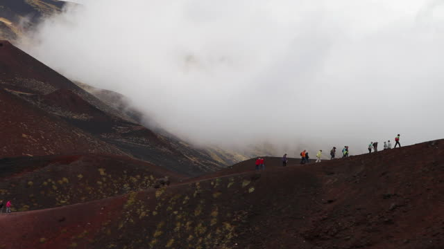 Mount Etna, tourists walking on the volcanic rocks on the mountain