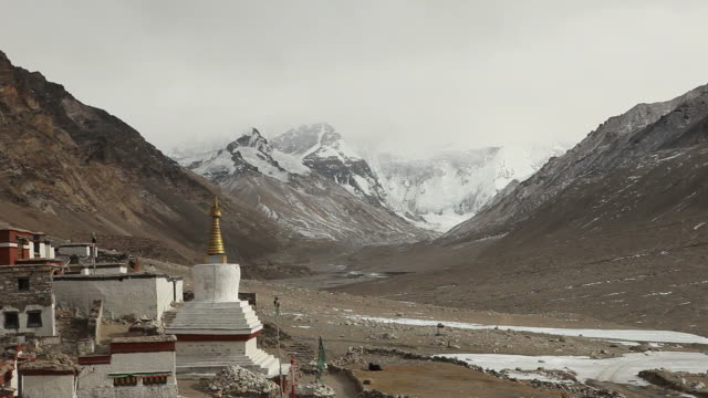 mount everest covered by clouds with the rongphuk monastery - monastery stock videos & royalty-free footage