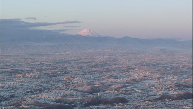 Mount Fuji and the city of Tokyo are covered with snow.
