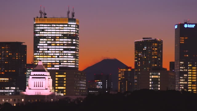 mount fuji appears during the sunset among the high-rise office buildings and diet of japan building in nagatacho chiyoda ward tokyo japan on dec. 26 2017. image was taken from marunouchi district chiyoda ward. - mese video stock e b–roll