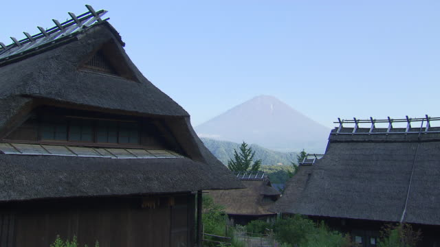 mount fuji looms in the distance of a group of thatched roof houses. - thatched roof stock videos & royalty-free footage
