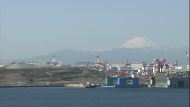 mount fuji looms on the distant horizon from the pedestrian walkway on the tokyo gate bridge. - ariake sea stock videos and b-roll footage
