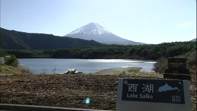 Mount Fuji looms over Lake Saiko and its nameplate in the Fuji Hakone Izu National Park in Yamanashi, Japan.