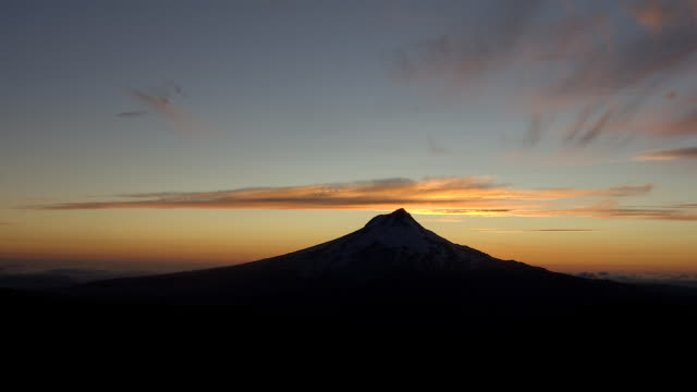 mount hood silhouetted against golden sunset and clouds - portland oregon sunset stock videos & royalty-free footage