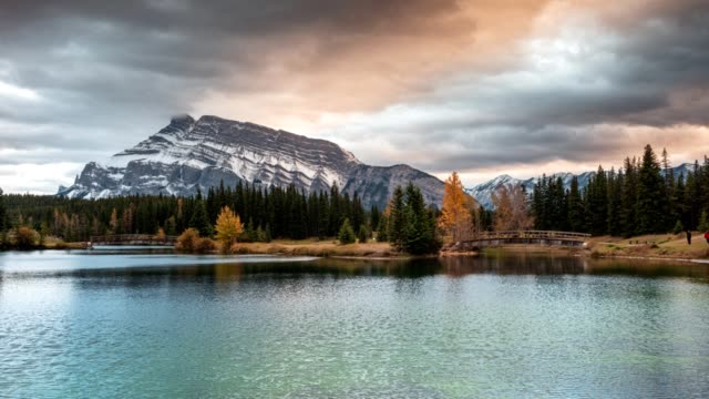 mount rundle with wooden bridge in autumn park at cascade ponds, banff national park - pond stock videos & royalty-free footage