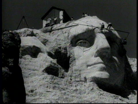 mount rushmore goes into fifth year of construction / washington's head nears completion / workers standing on the face of the monument / workers... - マウントラシュモア国立記念碑点の映像素材/bロール