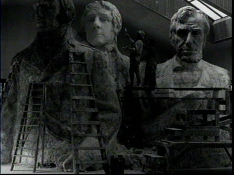 mount rushmore model unveiled / borglum working on models with ladders and scaffolding / borglum applies plaster to jefferson's head / artist works... - マウントラシュモア国立記念碑点の映像素材/bロール