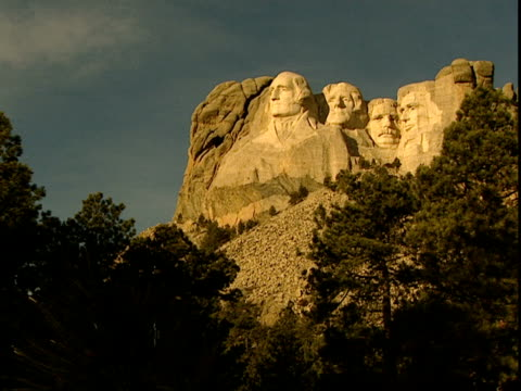 vidéos et rushes de mount rushmore stands above the tree line. - monument national du mont rushmore