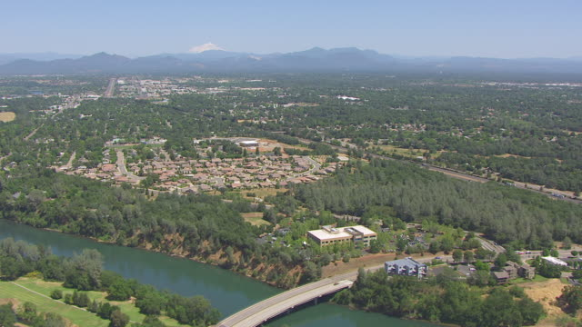 WS AERIAL POV Mount Shasta in background and houses and trees in foreground at California