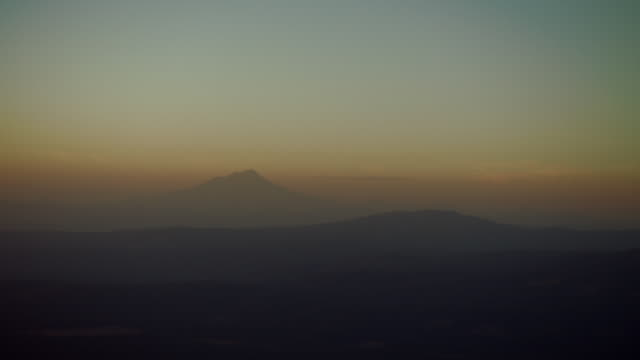 mount shasta silhouetted at against pale orange sky at sunset. - mountain range stock videos & royalty-free footage
