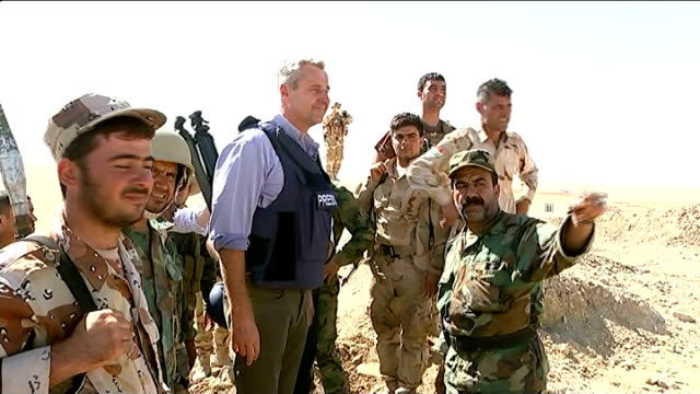 mass evacuation called off; iraq: ext reporter stands talking with group of kurdish soldiers in desert area - sinjar mountains stock videos & royalty-free footage
