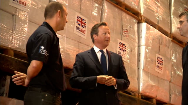 thousands flee to refugee camps / british aid drop gloucestershire david cameron in warehouse with uk aid parcels behind uk aid sign boxes of aid in... - ninawa stock videos & royalty-free footage