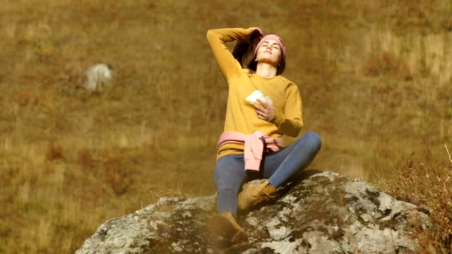 mountain adventure. young woman resting on the rock in the sun - named wilderness area stock videos & royalty-free footage