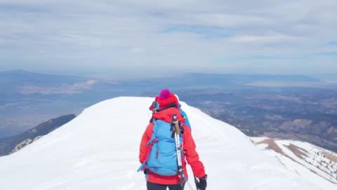 vídeos y material grabado en eventos de stock de equipo de escalada alpina de montaña se está moviendo hacia arriba en el pico de la montaña de gran altitud en invierno - moverse hacia arriba