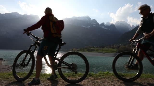 マウンテン バイク カップルが過去の湖日の出サイクルします。 - トレンティーノ点の映像素材/bロール