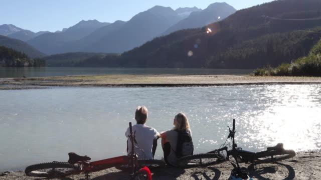 vídeos y material grabado en eventos de stock de mountain bike couple look off from mountain river edge - varón