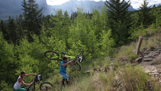 Mountainbike-Ehepaar schiebt Fahrräder auf steilen Weg
