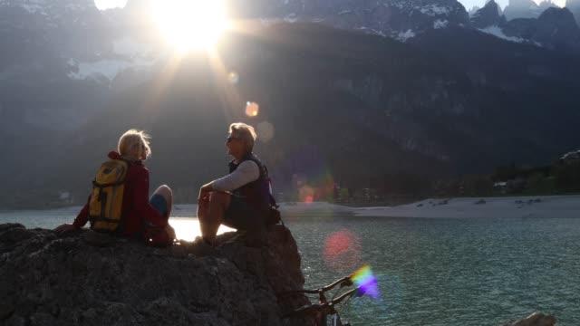 vídeos y material grabado en eventos de stock de par de bicicletas de montaña relajarse en roca sobre el lago al amanecer - mountain bike