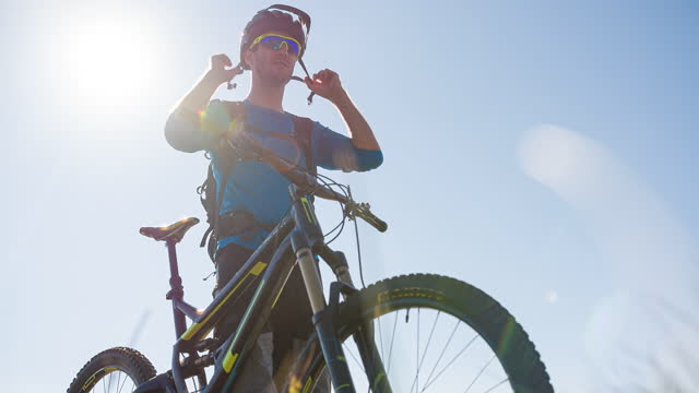 mountain bike cyclist getting ready for a ride, putting on helmet - mountain biking stock videos & royalty-free footage