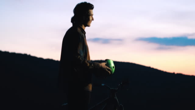 Mountain bike cyclist putting on his cycling helmet and starts riding at sunset.