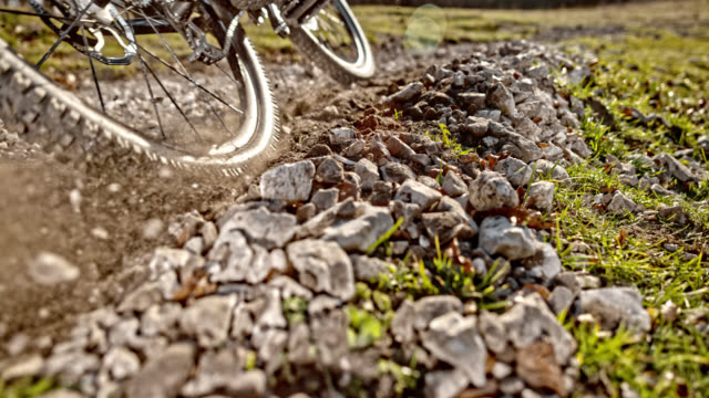 slo mo mountain bike pushing gravel into the air in sunshine - gravel stock videos & royalty-free footage