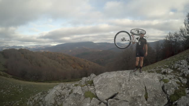 Mountain bike rider holds his bicycle in his shoulders while looking at the horizon in a mountain enviroment while camera approaches him in a steady shot