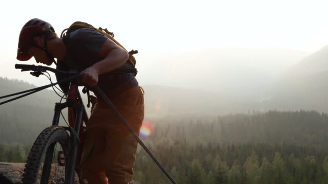 Mountain bike rider lowers from rope, on mountain ridge crest