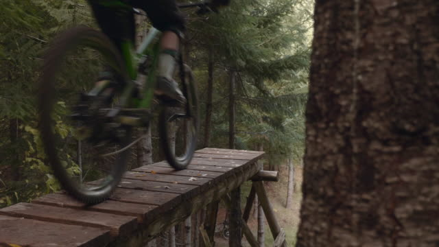 4k slo mo: mountain bike rider riding off ramp - mountain bike stock videos & royalty-free footage