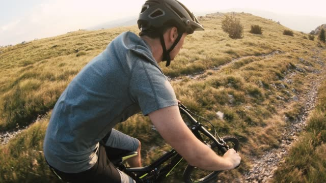 mountain bike rider speeding downhill across rocky mountain landscape on a sunny day - recreational horseback riding stock videos & royalty-free footage