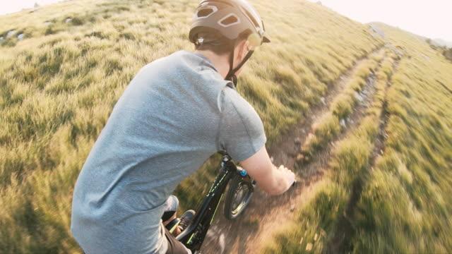 vídeos de stock e filmes b-roll de mountain bike rider speeding downhill across rocky mountain landscape on a sunny day - cavalgada de lazer