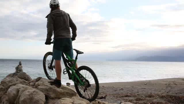 vídeos de stock, filmes e b-roll de mountain biker arrives at rock stack above empty beach, looks out to sea - coluna de calcário marítimo