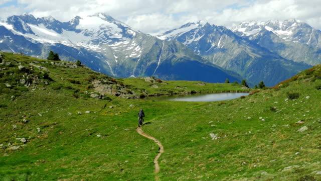 mountainbiker, die ankunft in alpinen see cinemagramm - motorradfahrer stock-videos und b-roll-filmmaterial