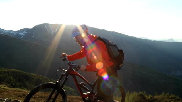 Mountainbiker steigt alpine Steigung Sonnenaufgang über dem fernen Berge