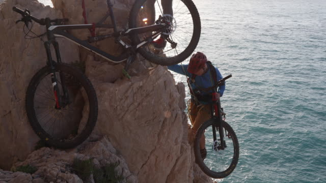 mountain biker ascends cliff to belayer above - corda video stock e b–roll