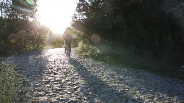 mountain biker ascends cobblestone path, sunrise - eskapismus stock-videos und b-roll-filmmaterial