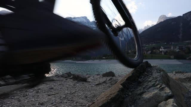 Mountain biker ascends lakeshore rocks at sunrise