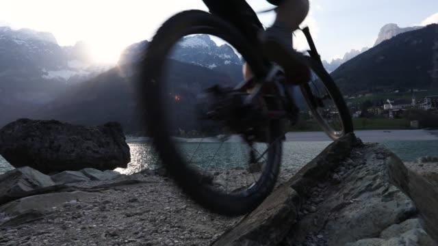 山のバイカーは日の出湖畔岩を登る - トレンティーノ点の映像素材/bロール