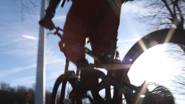 mountain biker ascends leafy slope below wind turbines - energia rinnovabile video stock e b–roll