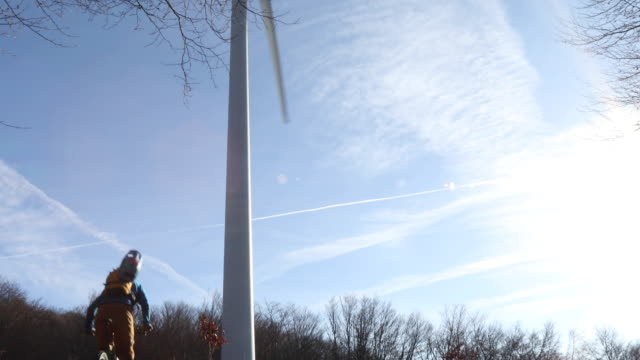 mountain biker ascends leafy slope below wind turbines - sustainable energy stock videos & royalty-free footage