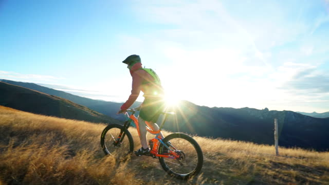 Mountain biker ascends mountain ridge at sunrise