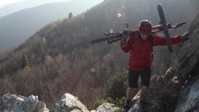 mountain biker ascends rock ridge, above mountains - pericolo video stock e b–roll