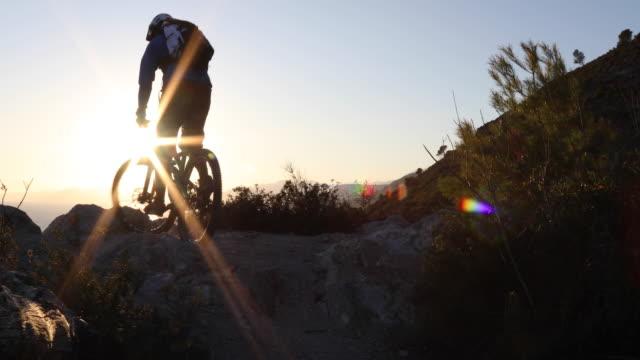 Mountain biker ascends rock ridge, pauses on summit