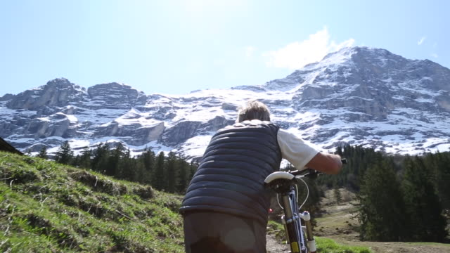 mountain biker ascends steep mountain slope below eiger - steep stock videos & royalty-free footage