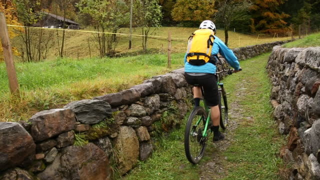 Mountain biker ascends trail between rock walls