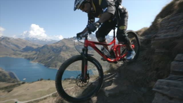 mountain biker biking downhill on a rocky trail in the mountains. - slow motion - effort stock videos & royalty-free footage