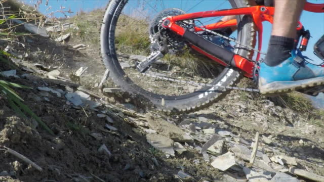Mountain biker biking downhill on a rocky trail in the mountains. - Slow Motion