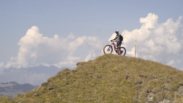 Mountain biker biking to the top of a hill in the mountains. - Slow Motion